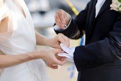 Braut, die ihrem Bräutigam mit seinen Manschettenknöpfen hilft stockfotografie