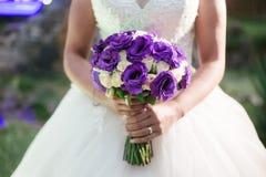 Braut, die ihren Blumenstrauß im Garten hält lizenzfreie stockbilder