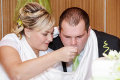 Braut, die ihren Bräutigam mit Löffel auf dem Hochzeitsmittagessen einzieht stockfotos