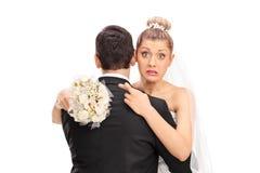 Braut, die ihren Ehemann mit ihren Fingern gekreuzt umarmt Stockfotos