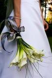 Braut, die ihren Hochzeit Blumenstrauß durch ihre Seite hält Lizenzfreies Stockfoto