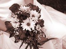 Braut, die ihren Hochzeitsblumenstrauß gegen ihr Kleid hält Stockfoto