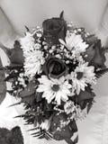 Braut, die ihren Hochzeitsblumenstrauß gegen ihr Kleid in Schwarzweiss hält Lizenzfreie Stockfotografie