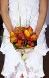 Braut, die ihren Orchideeblumenstrauß zeigt Stockfotografie