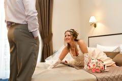 Braut, die ihren Schatz auf Bett wartet Stockbild