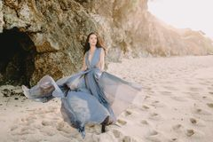 Braut, die im blauen Hochzeitskleid im Strand an den Sonnenuntergang- oder Sonnenaufgangfarben aufwirft Blonde Frau des Art und W Lizenzfreie Stockfotos