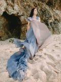 Braut, die im Hochzeitskleid im Strand an den Sonnenuntergang- oder Sonnenaufgangfarben aufwirft Blonde Frau des Art und Weisebau Lizenzfreie Stockbilder