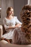 Braut, die im weißen Kleid ordentlich den Spiegel sitzt Stockfoto