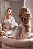Braut, die im weißen Kleid ordentlich den Spiegel sitzt Stockfotografie