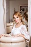 Braut, die im weißen Kleid ordentlich den Spiegel sitzt Lizenzfreies Stockfoto