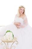 Braut, die mit dem Blumenstrauß lokalisiert auf Weiß sitzt Stockfotos