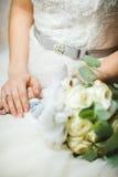 Braut, die mit den gekreuzten Händen im Ehering sitzt lizenzfreie stockbilder