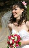 Braut, die mit Schleier und Blumenstrauß lacht stockfotografie