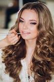 Braut, die morgens Make-up in einem Raum tut der Make-upkünstler, der Fachmann tut, bilden von der jungen Frau Make-upkünstler Stockbild