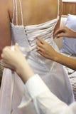 Braut, die oben in Hochzeitskleid geschnürt wird Lizenzfreies Stockbild