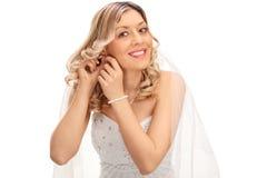 Braut, die Ohrringe auf ihre Ohren setzt Lizenzfreie Stockbilder