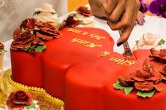 Braut, die rote Samt-Hochzeitstorte schneidet Lizenzfreies Stockbild