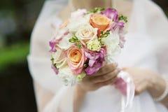 Braut, die schöne rosafarbene Hochzeitsblumen anhält Lizenzfreies Stockfoto