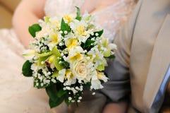 Braut, die schönen gelben Hochzeitsblumenstrauß anhält Lizenzfreies Stockfoto