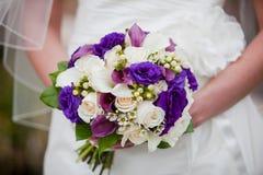 Braut, die schönen purpurroten und weißen Hochzeitsblumenstrauß von Blumen hält Stockfotografie