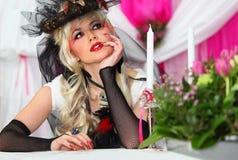 Braut, die schwarze Nettohandschuhe und ungewöhnlichen Hut trägt Stockbild