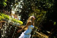 Braut, die Spaß mitten in dem Spray von Brunnen hat stockbild