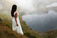 Braut, die unten auf nebeligem Berg schaut Lizenzfreies Stockbild