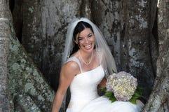 Braut, die unter Baum sitzt Lizenzfreie Stockfotografie