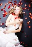 Braut, die unter rosafarbenen Blumenblättern liegt Stockfoto