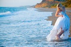 Braut, die weg von Seewellen läuft Stockbilder