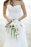 Braut, die weißen Orchideenblumen-Hochzeitsblumenstrauß hält Stockfotografie