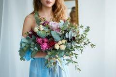 Braut in einem blauen Kleid mit Blumenstrauß Stockbild