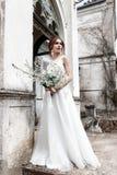 Braut in einem eleganten Kleid mit Blumenstrauß Stockfoto