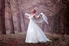 Braut in einem Hochzeitskleid im Wald draußen Lizenzfreie Stockbilder