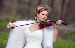 Braut in einem Hochzeitskleid mit einer Violine Lizenzfreie Stockfotos