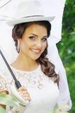 Braut in einem Hut mit Regenschirm Lizenzfreies Stockfoto