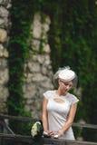 Braut in einem kleinen Hut schaut durchdachte Stellung auf der Brücke ist Stockbild