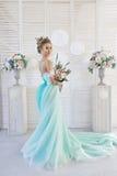 Braut in einem schönen Türkiskleid in Erwartung der Hochzeit Blondine im Spitzekleidermeergrün mit einem Blumenstrauß Glückliche  lizenzfreie stockfotos