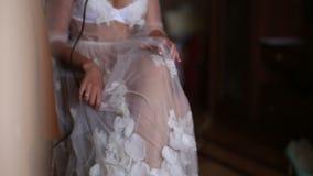 Braut in einem schönen weißen peignoir am Fenster stock video footage