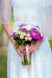Braut in einem weißen Kleid im Sommergrünpark mit einem Hochzeitsblumenstrauß in den Händen Stockbilder