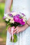 Braut in einem weißen Kleid im Sommergrünpark mit Hochzeitsblumenstrauß in den Händen Stockfotografie