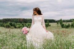 Braut in einem weißen Kleid und ein Blumenstrauß von Pfingstrosen in den Händen Lizenzfreies Stockbild