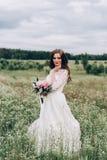 Braut in einem weißen Kleid und ein Blumenstrauß von Pfingstrosen in den Händen Lizenzfreie Stockfotografie