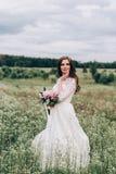 Braut in einem weißen Kleid und ein Blumenstrauß von Pfingstrosen in den Händen Lizenzfreie Stockfotos