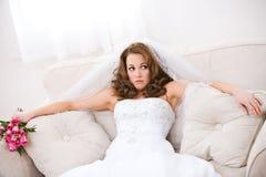 Braut: Gestörte Braut sitzt auf Couch mit Blumenstrauß Lizenzfreies Stockfoto