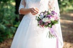 Braut hält einen Heiratsblumenstrauß, Hochzeitskleid stockfotos