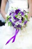 Braut hält den Hochzeitsblumenstrauß an Stockfotografie