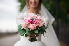 Braut hält einen Hochzeitsblumenstrauß Lizenzfreie Stockfotos