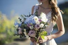 Braut hält Hochzeitsblumenstrauß auf Naturhintergrund stockfotos