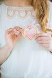 Braut hält Hochzeitsplätzchen Stockbild